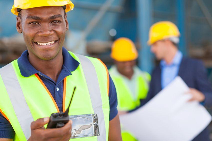 happy african american industrial worker with walkie talkie on site
