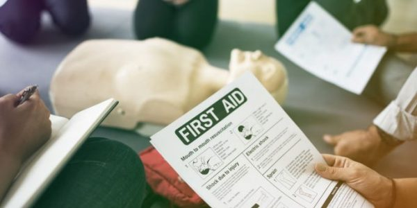 Group of people CPR First Aid training course with first aid ins