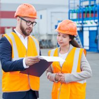 Waist up portrait of two modern factory workers wearing hardhats discussing production over clipboard outdoors, copy space